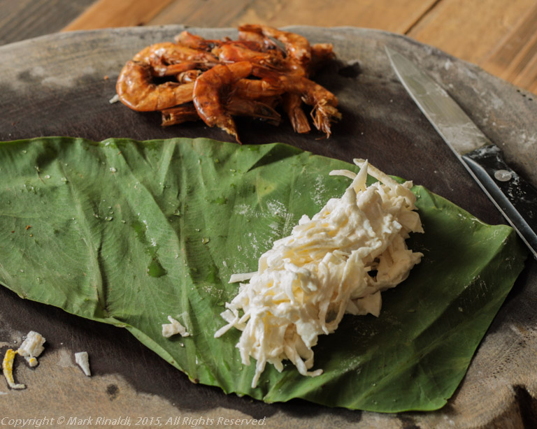 Sheets of taro leaf are filled with grated taro root and rolled like little cigars.